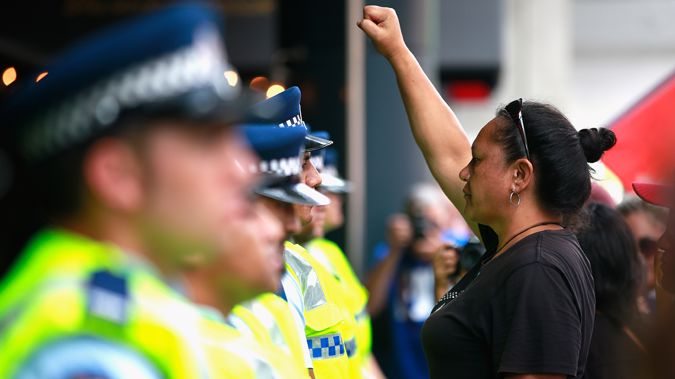 An anti-TPP protester confronts the police guarding the Sky City Convention Centre where the free trade deal was being signed on February 4, 2016 (Getty Images)