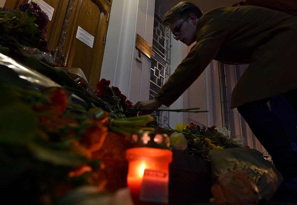 A man places flowers outside the Belgian embassy in Moscow.