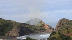 A second helicopter has been sent to Piha where a number of homes are at risk from a large scrub fire. (Alistair Wilkinson/Twitter)