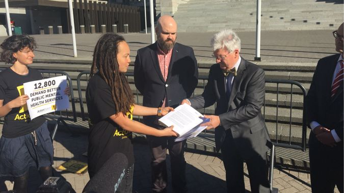 Representatives from lobby group Action Station deliver the open letter to Associate Health Minister Peter Dunne on the steps of Parliament (Photo / Georgia Nelson)