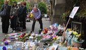 Members of the public pause to look at floral tributes and messages as the working day begins today in Manchester.  (Getty)