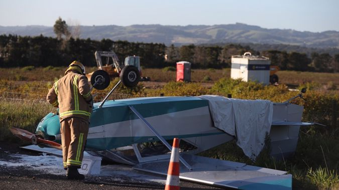 A fireman inspects the wreckage of the light plane that crashed on Runciman Road in Pukekohe East. (Jason Oxenham)