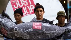 Greenpeace activists place a large mock-up of a SEALECT canned tuna in front of the Thai Union Headquarters, in Bangkok, to challenge the company to change their practices. (Photo / Supplied)