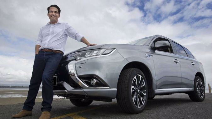 Transport Minister Simon Bridges, pictured with his Mitsubishi Outlander PHEV plug-in hybrid, says the Government won't follow the UK in banning petrol and diesel cars from 2040. (Photo / file)