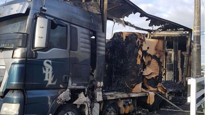 A car burst into flames when it crashed into the back of a large truck parked on the side of the road. (Supplied)
