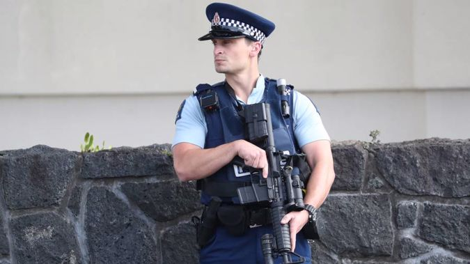 An armed police officer stands guard in Greenlane. (Photo / Jason Oxenham)