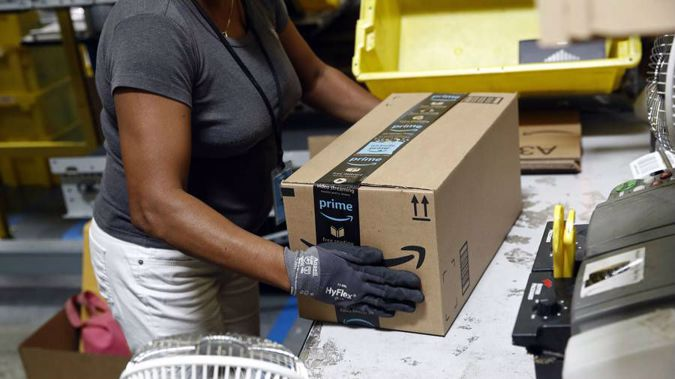 Worker at an Amazon fulfillment centre in Baltimore applies tape to a package before shipment. Labour will be bringing in GST on goods bought online. (Photo / AP)
