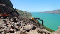 Dangling digger excavating slope above Christchurch road