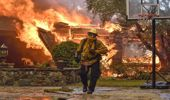 Firefighters work to extinguish a fire at a home as they battle a wildfire in Anaheim Hills. (Photo \ AP)