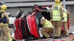 Firefighters work to free two people trapped in a vehicle involved in a two-vehicle crash at Maheno, 14km southwest of Oamaru, yesterday. (Photo / Daniel Birchfield)