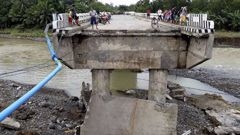 People gather on a bridge which was damaged by the onslaught of the flooding brought about by tropical storm Tembin in the Philippines. Photo / AP