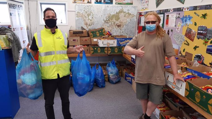 Cameron Webb (left), general manager operations for Deejays, and Randwick Park resident Dave Tims get food parcels ready for tomorrow's vaccination centre. (Photo / Supplied)