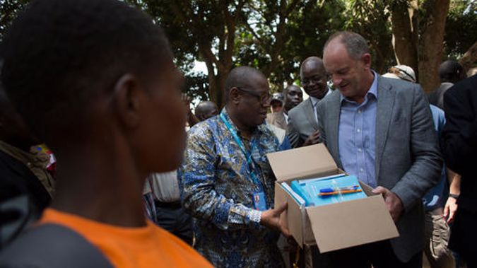United Nations Special Representative for South Sudan David Shearer (right) and UNICEF Representative in South Sudan Marimba Mdoe (centre) distribute books and pens to children formerly associated with an armed group. (Photo/ Karel Prinsloo)
