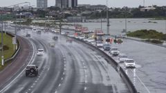 South bound motorists are forced to use one lane of the Auckland Motorway before the harbour bridge after the high tide and strong on shore winds caused several lanes to be under water. (Picture / Greg Bowker)