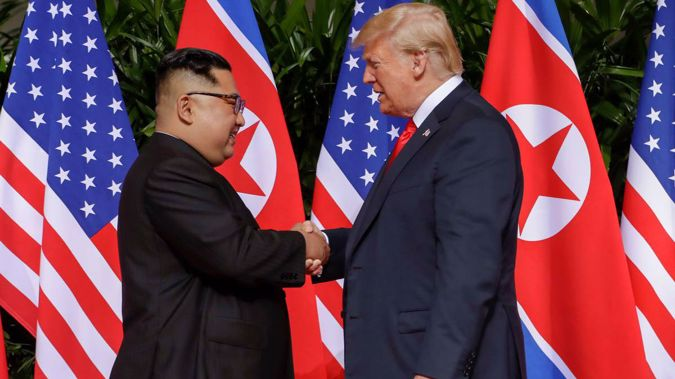 Kim Jong Un and Donald Trump shake hands for the cameras as the world watches. Photo / AP