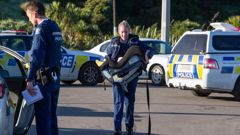 A police officer carries the baby in a car seat after rescuing it from a car involved in the police chase. Photo / Mark Mitchell