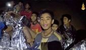 The boys smile as Thai Navy SEAL medic help injured children inside a cave in Mae Sai. (Photo / AP)