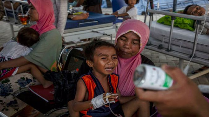 A boy cries while receiving treatment at an emergency hospital following Sunday's earthquake in Lombok, Indonesia. (Photo: Getty)