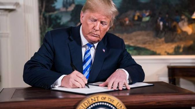 President Donald Trump signs a memorandum withdrawing the US from the Iran nuclear deal. Photo / Washington Post