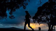 As the sun rises, runners compete in the North Shore Marathon on Sunday morning. Photo / Brett Phibbs