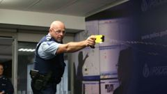 Sergeant Darrin Putt demonstrating the use of a taser during Police National Headquarters. (Photo: Mark Mitchell)