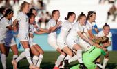 New Zealand players embrace goalkeeper Anna Leat after she scores the final penalty during a penalty shootout against Japan. (Photo / AP)