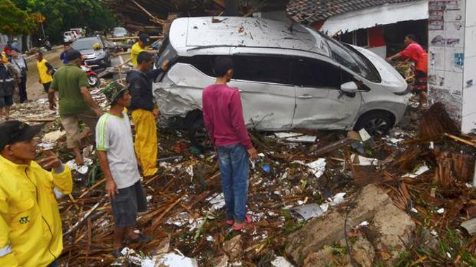 People inspect the wreckage of a car swept away by a tsunami in Carita, Indonesia. Photo / AP