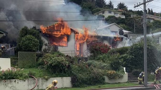 Fire crews work to put out a fire that destroyed a Reed St, Oamaru, home and set alight a neighbouring property yesterday. Photo / Logan Harris