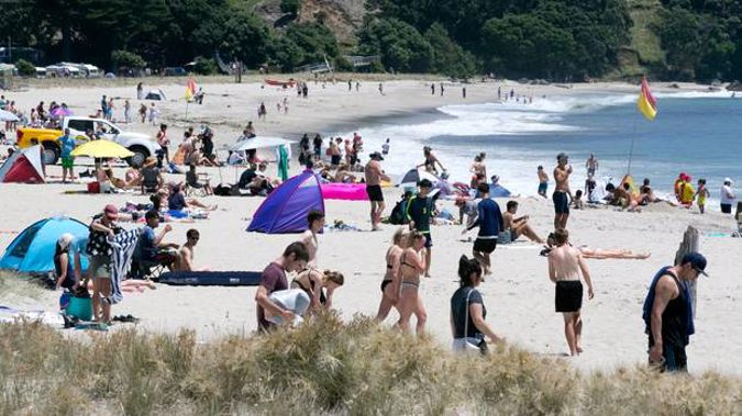 Beachgoers at Mt Maunganui enjoying the traditional blue skies and sunshine. Photo / Alan Gibson