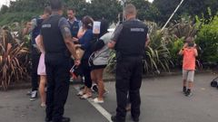 The infamous travellers talk to Police and Immigration officers in Hamilton. (Photo / Belinda Feek)