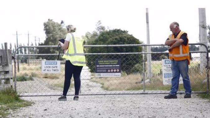 A WorkSafe NZ official, watched by another official examines the gate through which a 3-year-old is thought to have passed before drowning. Photo / Giordano Stolley