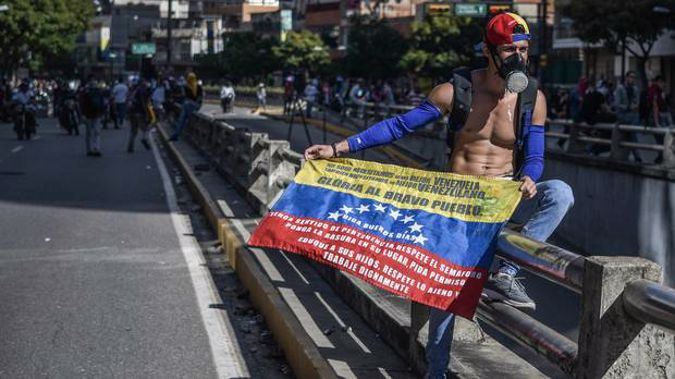 A demonstrator seen holding the Venezuelan flag while wearing a gas mask during a demonstration against President Nicolas Maduro's policies. Photo / Getty Images