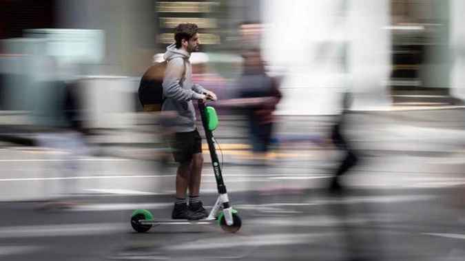 An Aucklander riding a Lime e-scooter around the city. (Photo / Greg Bowker)