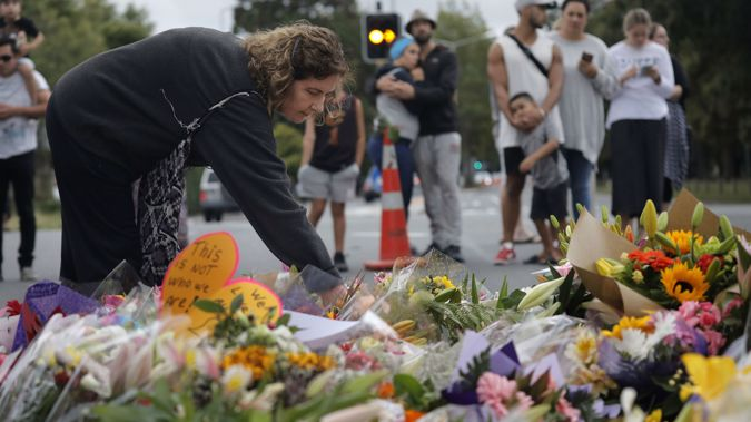 Mourners leave flowers at a memorial for the victims. (Photo / AP)