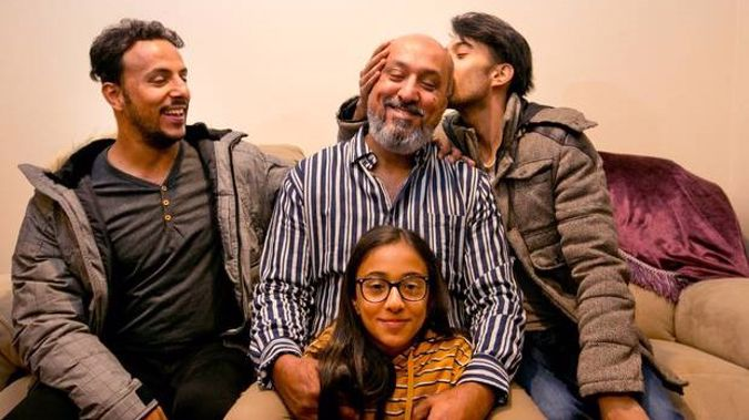 Khaled Al-Jammali gets a kiss from his son, Mahmoud Al-Jammali, right, while his other son, Hamoud Al-Jammali, left, and daughter Tala Al-Jammali are just happy to be with their father.