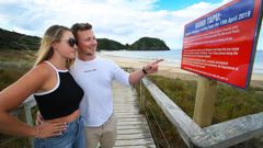 Visitors Kate Wardlaw from Taupo and Adam Howie from the United Kingdom reading one of the signs posted along Matapouri beach. Photo/Tania Whyte