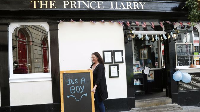A woman at the 'Prince Harry' puts out a sign celebrating the birth. (Photo / AP)