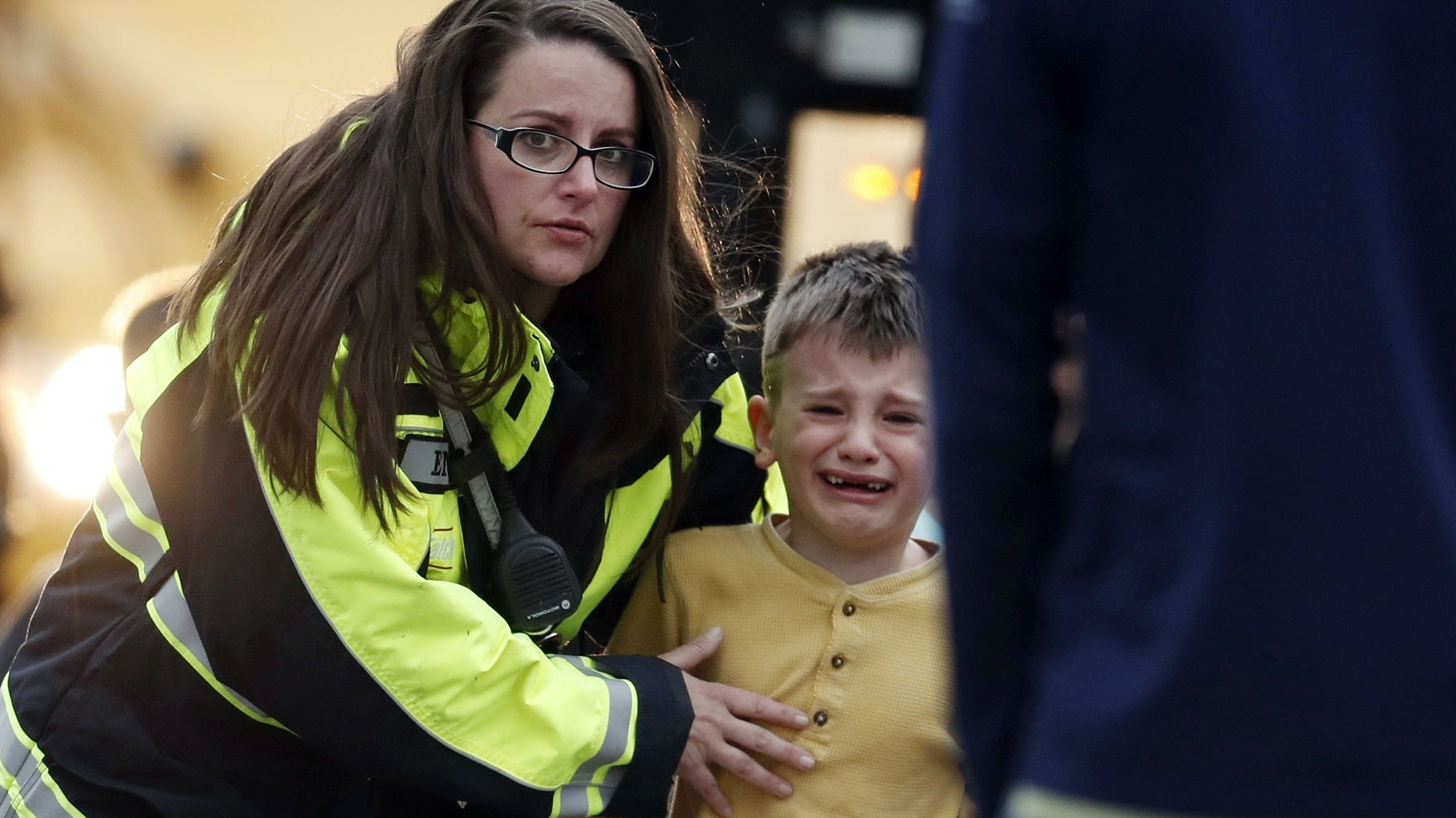 A young student is escorted to a recreation centre set up away from the shooting. (Photo / AP)