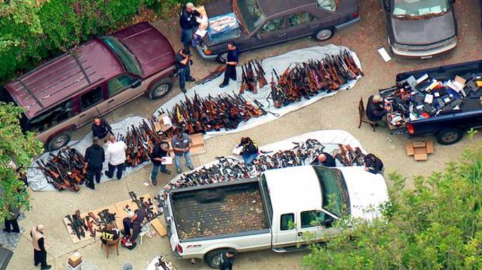 Investigators from the U.S. Bureau of Alcohol, Tobacco, Firearms and Explosives and the police inspecting a large cache of weapons seized at a Bel Air mansion. Photo / AP