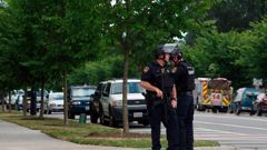 Virginia Beach Police Officers huddle near the intersection of Princess Anne Road and Nimmo Parkway following a shooting at the Virginia Beach Municipal Center. Photo / AP
