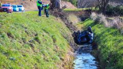 Two were trapped for a period of time in the car as it lay on its roof in the drain. (Photo / Paul Taylor)