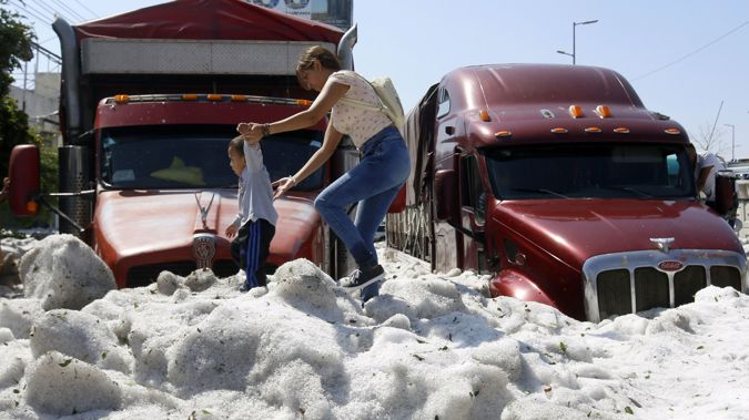Cars and vehicles were buried beneath the sudden hail. (AFP via CNN)
