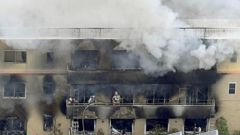 Firefighters work as smoke billows from a three-story building of Kyoto Animation in a fire in Kyoto, western Japan. Photo / AP