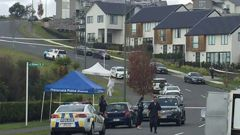 Police place a white tent over the body of a woman who was fatally stabbed. (Photo / NZ Herald)