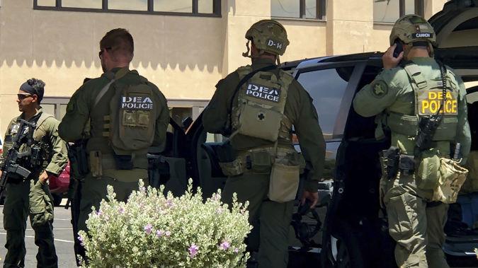 Law enforcement agencies descend on the scene of the crime. (Photo / AP)