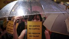 A woman holds an umbrella and a placard as people gather at Chater Garden to give support to the recent protests against the extradition bill, at the financial district in Hong Kong. Photo / AP