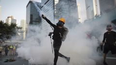 An anti-government protester throws back a tear gas canister fired by the police during a demonstration in Hong Kong. (Photo / AP)