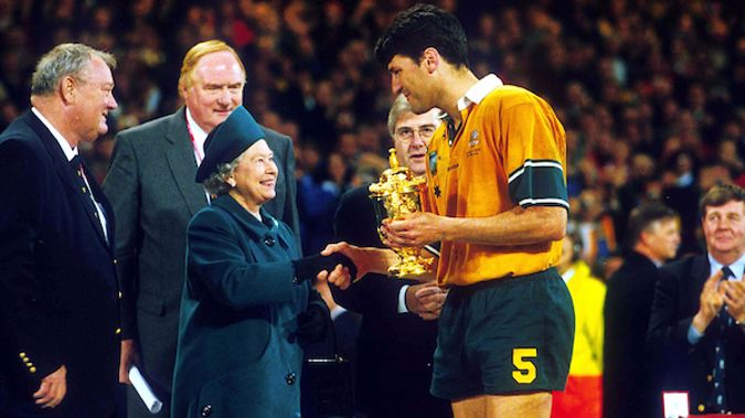 Australian captain John Eales is presented the William Webb Ellis Trophy by Queen Elizabeth II after winning the Rugby World Cup Final against France, November 6 1999, Cardiff, Wales. Australia won the match 35 - 12. (Photo: PHOTOSPORT)
