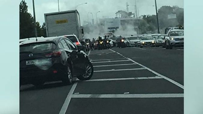 In a photo the members can be seen blocking the road as a car does a burnout behind them. Photo / Supplied