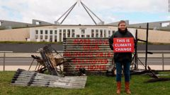 "Bushfire survivor Melinda Plesman delivers the message ""This is Climate Change"" outside Parliament House in Canberra. (Photo / Greenpeace via CNN)"